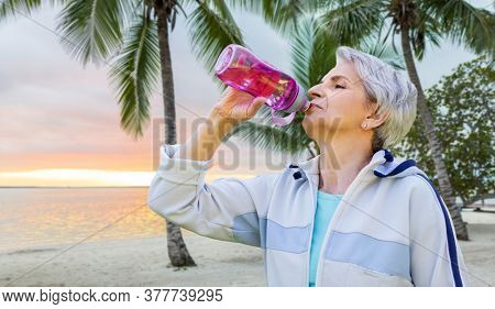 fitness, sport and healthy lifestyle concept - thirsty senior woman drinking water from bottle after exercising over tropical beach background in french polynesia