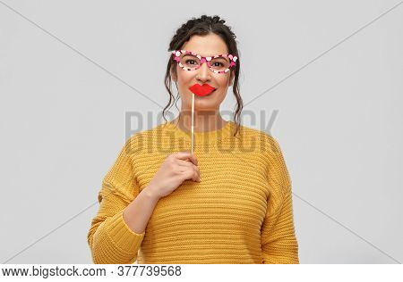 party props, photo booth and people concept - portrait of happy smiling young woman with pierced nose with big glasses and lips over grey background