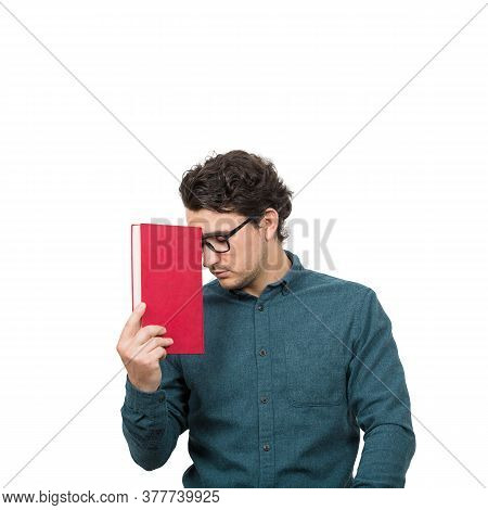 Tired Student Guy Looking Down With Pessimistic Emotion, Holding A Book, Isolated On White Backgroun