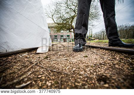 Bride And Groom Wedding Couple Feet With Weddingdress And Suit On A Country Road. High Quality Photo