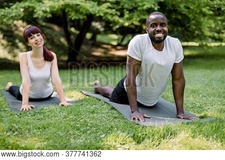 Horizontal Shot Of Young Multiethnic Couple Practicing Yoga Cobra Pose At Outdoors Summer Park. Afri