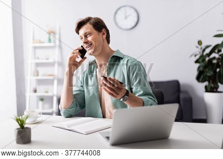 Selective Focus Of Smiling Teleworker Talking On Smartphone Near Laptop And Notebook In Living Room,