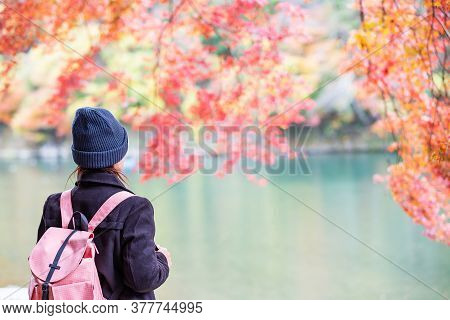 Happy Woman Tourist Looking Colorful Leaves And Katsura River In Arashiyama, Young Asian Traveler Vi