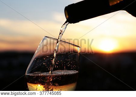 White Wine Pouring From A Bottle Into The Glass On Beautiful Sunset Background, Selective Focus. Con