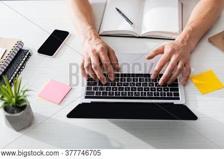 Top View Of Man Typing On Laptop With Blank Screen With Stationery And Smartphone On Table At Home,