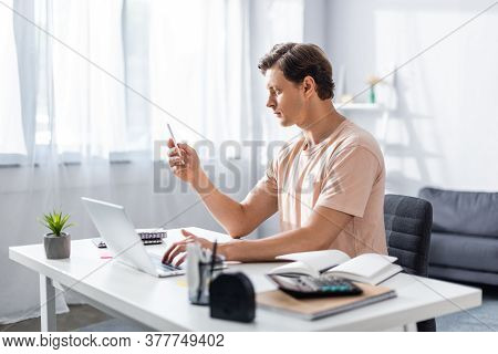 Teleworker Looking At Cellphone While Typing On Laptop, Sitting On Chair At Home, Earning Online Con