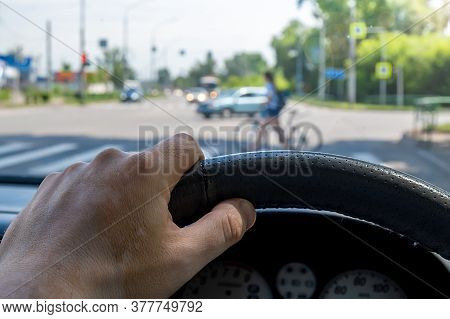 The Driver Hand At The Wheel Of A Car Against The Background Of A Pedestrian Crossing And A Pedestri