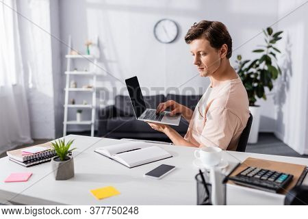 Concentrated Freelancer Using Laptop And Looking At Notebook On Table At Home, Earning Online Concep