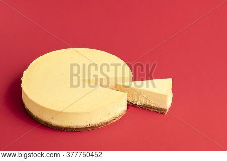 Homemade Classic Cheesecake With One Slice, Isolated On A Red Seamless Background. Creamy Dairy Cake