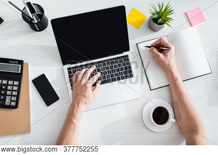 Top View Of Man Typing On Laptop And Writing On Notebook Near Cellphone And Stationery On Table, Ear