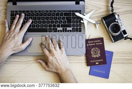 Male Hands Typing On Modern Laptop For Booking An Airplane Flight - Man Plans Couple Tour With Passp