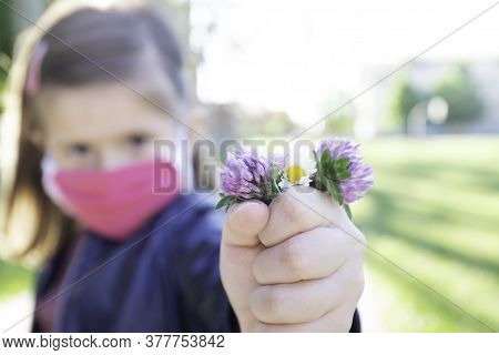 Little Hopeful Girl With Protective Mask Holding Bunch Of Wildflowers During Coronavirus Outbreak -