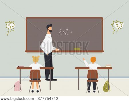 Male Math Teacher Explaining Multiplication To Elementary School Pupils Or Children Near Chalkboard.