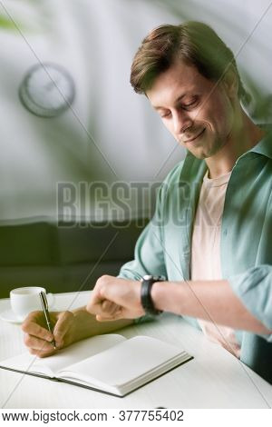 Selective Focus Of Smiling Freelancer Checking Time While Writing On Notebook Near Cup Of Coffee, Co