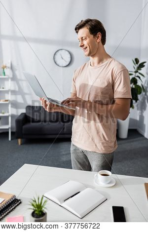 Freelancer Using Laptop Near Table With Stationery And Coffee Cup At Home, Earning Online Concept
