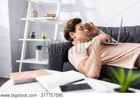 Selective Focus Of Teleworker Using Laptop While Lying On Couch Near Notebooks And Smartphone On Cof