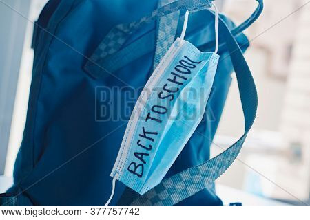 closeup of a green bookbag and a blue surgical mask with the text back to school written in it, depicting the need to prevent the infection at school in the covid-19 pandemic situation