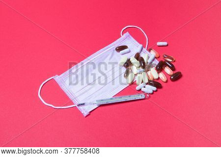 Pink Medical Face Mask, Mercury Thermometer And Tablets On Red Background.
