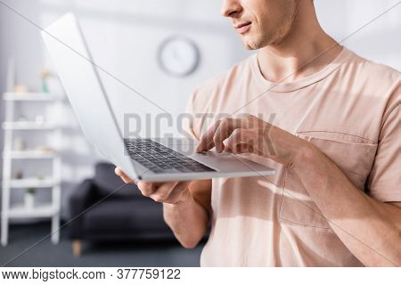 Cropped View Of Freelancer Holding And Typing On Laptop At Home, Earning Online Concept