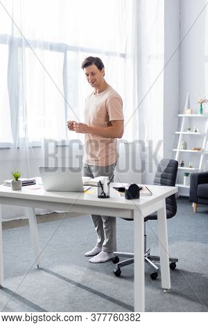 Smiling Freelancer Standing In Front Of Laptop On Table With Stationery At Home, Earning Online Conc