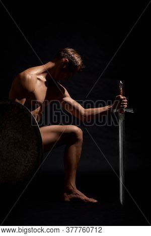 Side View Of Young Strong Warrior Standing On Knee And Looking Down. Muscular Half Naked Athlete Pos