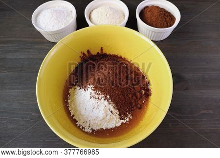 Flour And Cocoa Powder In A Mixing Bowl With Bowls Of Ingredients For The Concept Of Cooking Healthy