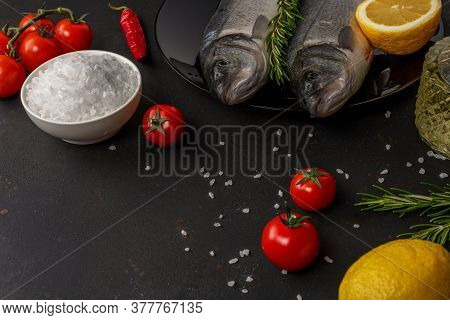 Two Fresh Seabass Fishes With Rosemary And Vegetable On A Black Plate.