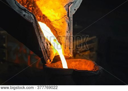 Molten Metal Flows Out Of A Furnace In A Smelter.