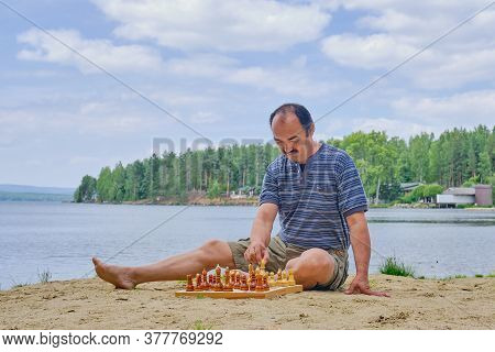 Senior Asian Man Making A Move In A Game Of Chess And Sitting On The Beach Near The Lake.
