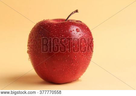 Red, Ripe, Juicy, Beautiful Apple With Drops. On A Yellow, Delicate Background. Copyspace.