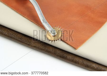 The Leather Is Brown, The Fabric Is White For Sewing. A Tool For Sewing Leather. In The Background.