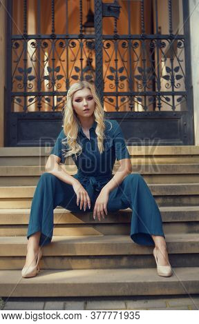 A Full-length Girl Sits On The Stairs In A Long Blue Overalls. The Girl Looks Into The Camera With A