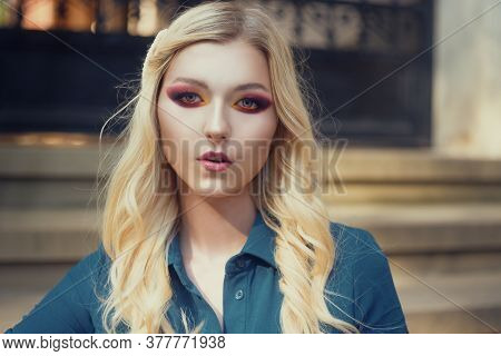Blonde With Beautiful Smoky Eyes Makeup. Bright Red Shadows On A Beautiful Female Face. A Model On T