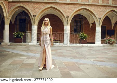Beautiful Lady In Luxurious Pink Ballroom Dress. Blond Walking Along The Old Castle. The Blonde Look