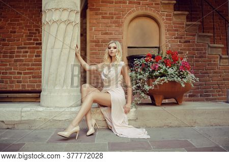 Gorgeous Girl Sits In A Castle On The Street On A Journey. A Blonde In A Long Delicate Dress With A