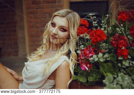 Portrait Of A Pensive Blonde Near Red Flowers. Professional Makeup, Red Smoky Eyes. Girl With A Cute