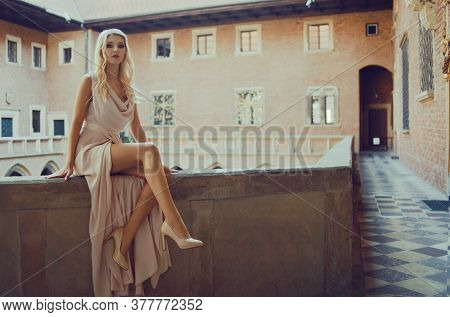 A Beautiful Girl With Long Legs Is Sitting On The Balcony In The Castle. Princess On The Balcony On