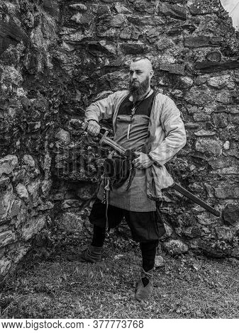 Viking Warrior Draws His Sword In Front Of A Stone Wall, Image Of Historical Re-enactment In Black A