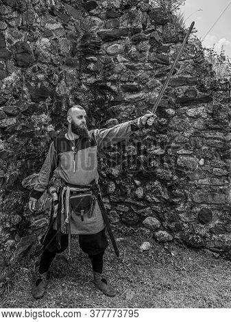 Viking Warrior Draws His Sword In Front Of A Stone Wall