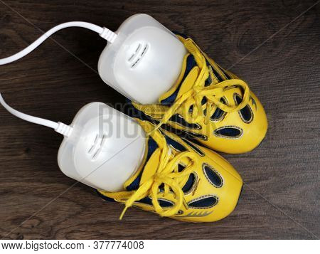 Electric Ultraviolet Shoe Dryer And Yellow Sneakers Top View