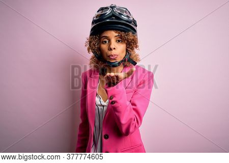 African american motorcyclist woman with curly hair wearing moto helmet over pink background looking at the camera blowing a kiss with hand on air being lovely and sexy. Love expression.