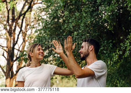 Healthy Fit And Sportive Couple Hi Five And Smile Face In Nature At Summer Day. Athletic Couple Jogg