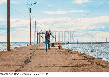 A Girl And A Labrador Run Merrily Along The Sea Pier. Sports And Outdoor Activities With Labrador