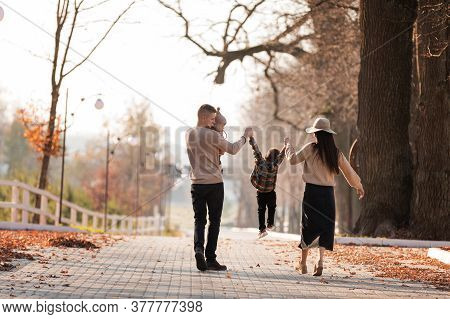 Happy Young Family With Two Little Children Walking And Having Fun In Autumn Park On Sunny Day.