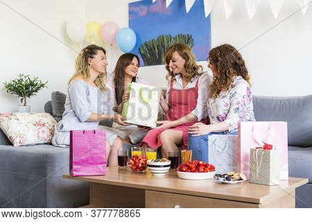 A Group Of Smiling Friends Are Sitting, Celebrating Baby Shower And Opening Presents. It Is Atmosphe