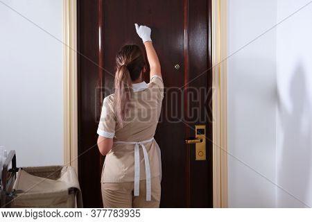 Room Service. A Uniformed Maid Knocks On The Door Of The Hotel Room. Trolley With Shower Accessories