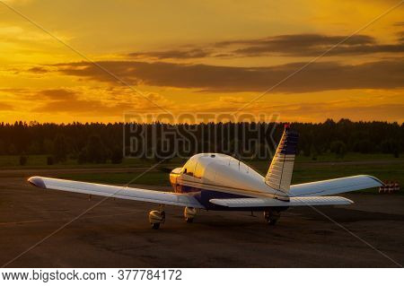 Rear View Of A Parked Small Plane On A Sunset Background. Silhouette Of A Private Airplane Landed At
