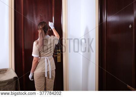 A Young Maid In Uniform Knocks On The Door Of The Room. Hotel Room Service. Trolley With Shower Acce
