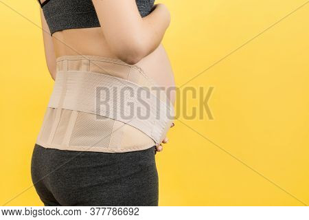 Back View Of Pregnant Woman Wearing Pregnancy Belt At Yellow Background With Copy Space. Close Up Of