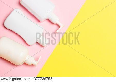 Set Of White Cosmetic Containers Isolated On Yellow Background, Top View With Copy Space. Group Of P